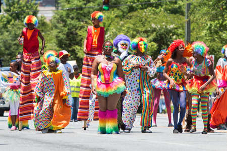 carnivale: Atlanta, GA, USA - May 28, 2016:  People wearing colorful clown costumes and walking on stilts participate in a parade celebrating Caribbean culture on North Avenue on May 28, 2016 in Atlanta, GA. Editorial