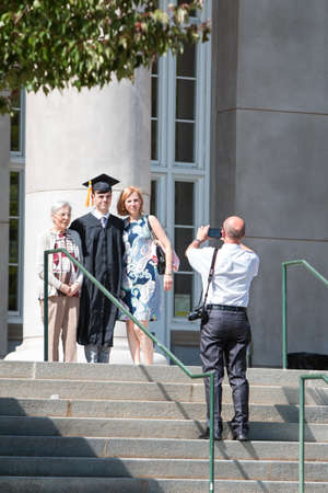 Athens, GA, USA - May 13, 2016:  A male graduate poses with family members for a photo before the graduation ceremony at the University of Georgia on May 13, 2016 in Athens, GA.