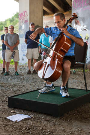 Atlanta, GA, USA - August 6, 2016:  A lone male cellist plays the cello under a highway overpass along the Atlanta Beltline as part of an arts demonstration for the Atlanta Ballets Wabi Sabi peformance, on August 6, 2016 in Atlanta, GA.