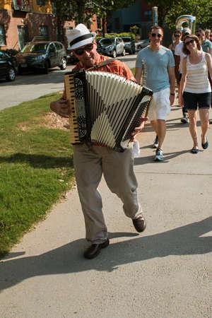 Atlanta, GA, USA - August 6, 2016:  An accordion player leads a group of spectators along the Atlanta Beltline to the next stop for the Atlanta Ballets Wabi Sabi performance, on August 6, 2016 in Atlanta, GA.