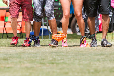 in unison: Atlanta, GA, USA - July 16, 2016:  The legs of four young adults walk in unison in a five-legged race, as part of the kids games played by adult teams at the Atlanta Field Day in the Old Fourth Ward Park, on July 16, 2016 in Atlanta, GA. Editorial