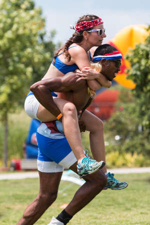 in unison: Atlanta, GA, USA - July 16, 2016:  An athletic man carries a woman piggyback as they race in one of the kids games played at Atlanta Field Day, at the Old Fourth Ward Park on July 16, 2016 in Atlanta, GA.