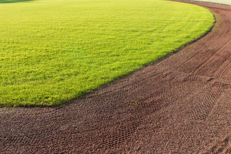 outfield: Outfield grass and warning track dirt of baseball field.