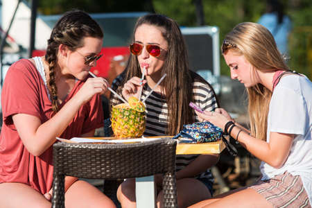 Kennesaw, GA, USA - August 27, 2016:  Female college students share sips of a fruity beverage from the inside of a pineapple while attending the Great Southern Food Truck Rally on August 27, 2016 in Kennesaw, GA.