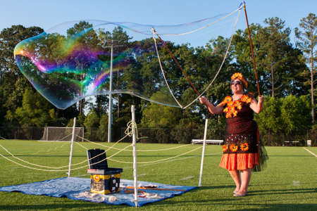 soapy water: Kennesaw, GA, USA - August 27, 2016:  A woman uses soapy water to create huge bubbles for people to enjoy at a festival on August 27, 2016 in Kennesaw, GA.