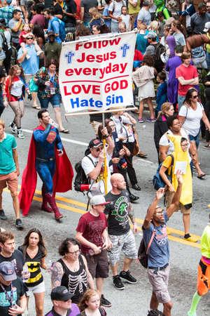 Atlanta, Ga, USA - September 3, 2016:  A man carrying a religious sign uses a bullhorn to preach the gospel to  a huge crowd of spectators and participants following the annual Dragon Con parade on September 3, 2016 in Atlanta, GA.