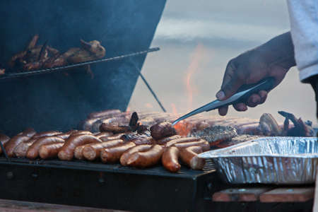 scrumptious: Various meats cook over open flame on grill Stock Photo