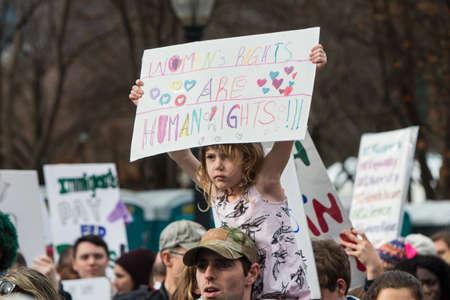 Atlanta, GA, USA - 21. Januar 2017: Ein Mädchen, das auf den Schultern ihres Vaters sitzt, trägt ein Zeichen, das Frauenrechte fördert, während Tausende am Atlanta-Marsch für soziale Gerechtigkeit und Frauen am Tag nach Präsident Trumps Einweihung am 21. Januar teilnehmen Standard-Bild - 71117406