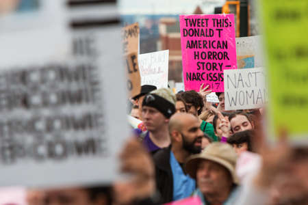 dissension: Atlanta, GA, USA - January 21, 2017:  A satirical sign that says Tweet This:  Donald T. American Horror Story stands out among the crowd, as thousands of protesters participate in the Atlanta march for social justice and women, the day after President T
