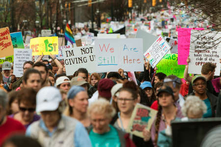 Atlanta, GA, USA - January 21, 2017:  A group of protest signs rise above the crowd as thousands of protesters walk in the Atlanta march for social justice and women, the day after President Trumps inauguration, on January 21, 2017 in Atlanta, GA.