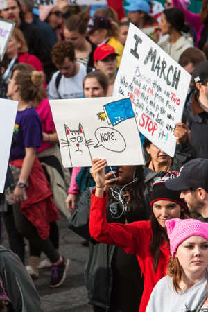 dissension: Atlanta, GA, USA - January 21, 2017:  A woman holds up a sign that is anti Trump, anti sexual harassment, as she and thousands of others participate in the Atlanta march for social justice and women, the day after President Trumps inauguration, on Januar