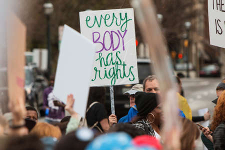 dissent: Atlanta, GA, USA - January 21, 2017:  A man holds up a sign that says Every body has rights as he walks in the Atlanta march for social justice and women, the day after President Trumps inauguration, on January 21, 2017 in Atlanta, GA. Editorial