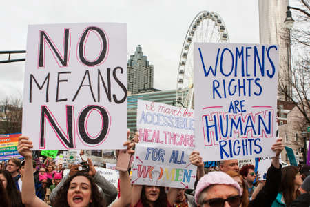 Atlanta, GA, USA - January 21, 2017:  Women hold up signs in support of womens rights, as thousands of protesters participate in the Atlanta march for social justice and women, the day after President Trumps inauguration, on January 21, 2017 in Atlanta, Editorial