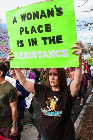 janu: Atlanta, GA, USA - January 21, 2017:  A woman carries sign that says A womans place is in the resistance as she and thousands of others participate in the Atlanta march for social justice and women, the day after President Trumps inauguration, on Janu