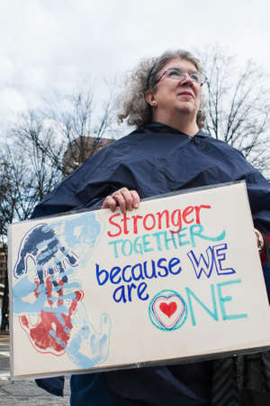dissension: Atlanta, GA, USA - January 21, 2017:  A woman holds a sign that says Stronger together because we are one as she prepares to participate in the Atlanta march for social justice and women, the day after President Trumps inauguration, on January 21, 2017