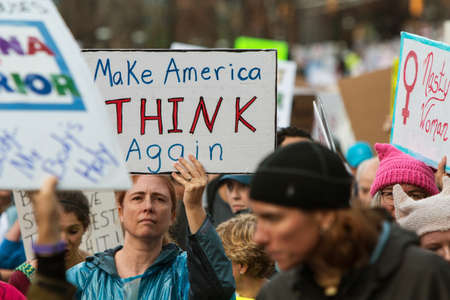 dissension: Atlanta, GA, USA - January 21, 2017:  A woman holds up sign that says Make America Think Again as she and thousands of others participate in the Atlanta march for social justice and women, the day after President Trumps inauguration, on January 21, 201 Editorial
