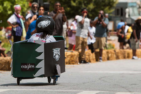 aplaudiendo: Atlanta, GA, USA - August 13, 2016:  A girl steers her homemade car downhill in the Cool Dads Rock Soap Box Derby in the Old Fourth Ward, on August 13, 2016 in Atlanta, GA.