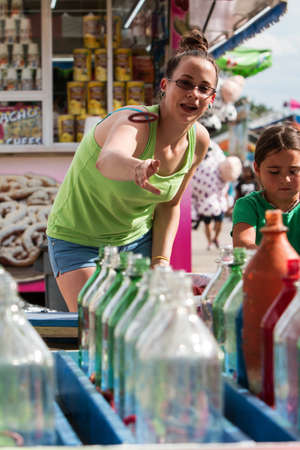 county fair: Lawrenceville, GA, USA - September 17, 2016:  A young woman tosses a ring at glass bottles in the ring toss game at the Gwinnett County Fair, on September 17, 2016 in Lawrenceville, GA. Editorial