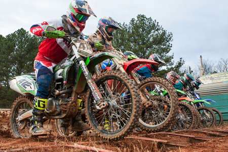 Monroe, GA, USA - December 3, 2016:  Riders lunge forward at the start of a motocross race at the Scrubndirt Mx track on December 3, 2016 in Monroe, GA. Editorial