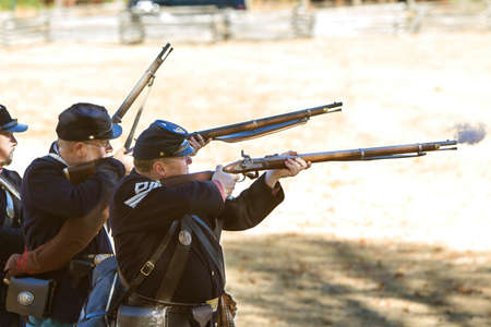 Kennesaw, GA, USA - November 20, 2016:  A small group of Civil War reenactors wearing union uniforms fire their muskets in a firing demonstration put on at Kennesaw Mountain National Battlefield Park, on November 20, 2016 in Kennesaw, GA. Editorial