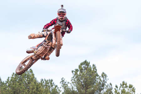 taker: Monroe, GA, USA - December 3, 2016:  A rider poses in midair after going over a jump in a motocross race at the Scrubndirt Track on December 3, 2016 in Monroe, GA.