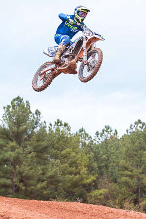 taker: Monroe, GA, USA - December 3, 2016:  A rider gets airborne after going over a jump in a motocross race at the Scrubndirt Track on December 3, 2016 in Monroe, GA.