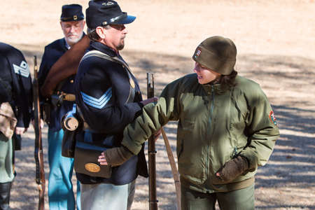 Kennesaw, GA, USA - November 20, 2016:  A young female National Park Ranger explains various components of a union soldiers uniform, as reenactors put on a firing demonstration at Kennesaw Mountain National Battlefield Park, on November 20, 2016 in Kenne