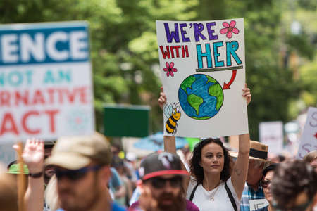 Atlanta, GA, USA - March 22, 2017:  A woman holds up a sign that says Were with her that points to a drawing of earth, as she takes part in the Atlanta March for Science near Candler Park on Earth Day on April 22, 2017 in Atlanta, GA. Editorial