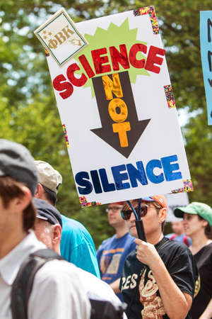 Atlanta, GA, USA - March 22, 2017:  A woman holds up a sign that says Science Not Silence as she walks in the Atlanta March for Science near Candler Park on Earth Day on April 22, 2017 in Atlanta, GA.