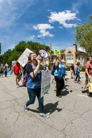 activism: Atlanta, GA - April 15, 2017:  A young woman yells through a bullhorn as she and other protesters walk in the Atlanta Tax March protesting President Trump not releasing his tax returns, on April 15, 2017 in Atlanta, GA. Editorial