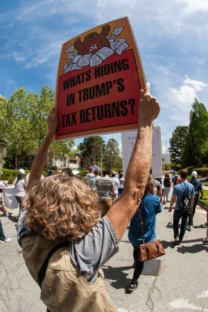 Atlanta, GA - April 15, 2017:  A woman holds sign that says Whats hiding in Trumps tax returns? as she walks in the Atlanta Tax March protesting President Trump not releasing his tax returns, on April 15, 2017 in Atlanta, GA.