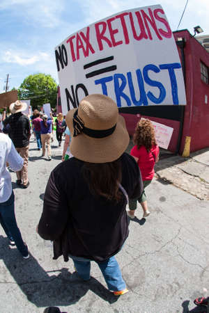 Atlanta, GA - April 15, 2017:  A woman holds sign that says No tax returns = no trust as she walks in the Atlanta Tax March protesting President Trump not releasing his tax returns, on April 15, 2017 in Atlanta, GA. Editorial