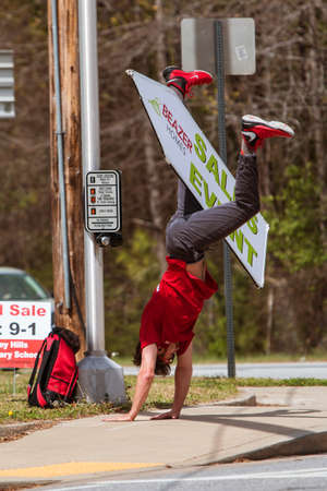 Atlanta, GA, USA - March 25, 2017:  A young man skillfully balances a sign between his legs as he performs a cartwheel, to promote a home selling event with signage on a street corner on March 25, 2017 in Atlanta, GA.
