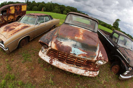 Rusted antique vehicles sit lined up in an auto junkyard Stock Photo