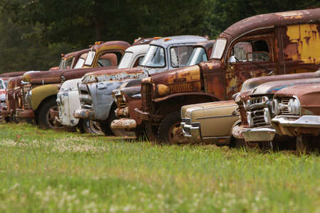 Gainesville, GA, USA - June 1, 2017:  A row of old, discarded cars and trucks sit lined up all in a row in a grassy junkyard field on June 1, 2017 in Gainesville, GA.