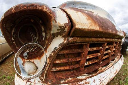 A broken headlight hangs from an old rusted junkyard vehicle Stock Photo