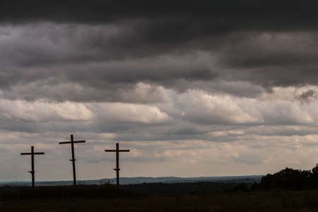 Three crosses in a North Georgia field stand against a dark, ominous sky.
