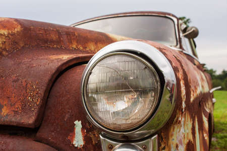 Cracked headlight on old rusted junkyard car 스톡 콘텐츠