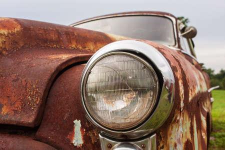Cracked headlight on old rusted junkyard car Foto de archivo