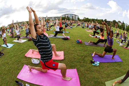 in unison: Atlanta, GA, USA - July 2, 2017:  Dozens of people do a yoga pose as they take part in a free group yoga class at the Old Fourth Ward Park on July 2, 2017 in Atlanta, GA. Editorial