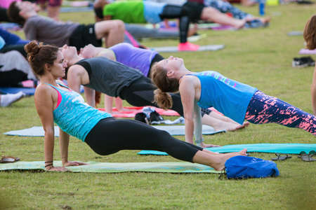 in unison: Atlanta, GA, USA - July 2, 2017:  Dozens of people do the reverse plank pose as they take part in a free group yoga class at the Old Fourth Ward Park on July 2, 2017 in Atlanta, GA. Editorial