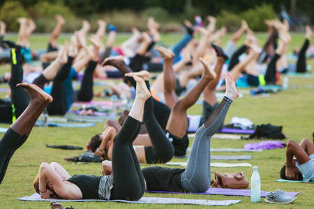 Atlanta, GA, USA - July 2, 2017:  Dozens of people do a yoga pose lying on their backs as they take part in a free group yoga class at the Old Fourth Ward Park on July 2, 2017 in Atlanta, GA.