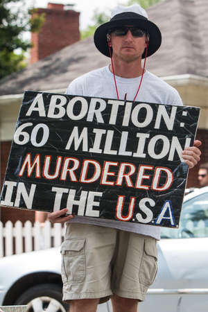 Atlanta, GA, USA - April 29, 2017:  A young man holds an anti-abortion sign reading Abortion:  60 million murdered in the USA, as he stages a one-man abortion protest before the Inman Park Festival Parade, on April 29, 2017 in Atlanta, GA.
