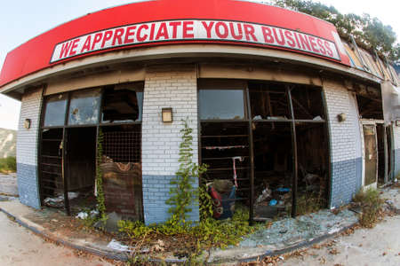Atlanta, GA, USA - September 23, 2017:  Fisheye view of a sign reading We appreciate your business at burned out, abandoned small business in Atlanta, GA.