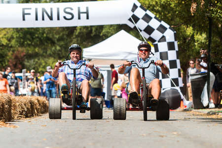Atlanta, GA, USA - September 23, 2017: Two men race each other on adult big wheels in a friendly competition at the East Atlanta Strut, a fall festival on September 23, 2017 in Atlanta, GA.