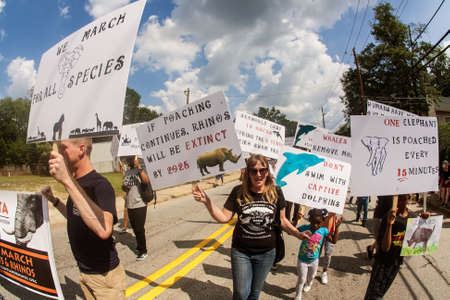 Atlanta, GA, USA - September 23, 2017:  A group of animal rights activists carry signs about rhinos and elephants as they walk in the East Atlanta Strut parade on September 23, 2017 in Atlanta, GA. 版權商用圖片 - 117650187