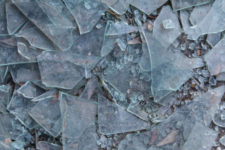 Broken glass litters pavement of vandalized building Stock Photo