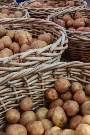 Vertical shot of potatoes in wicker baskets on sale at local farmers market.