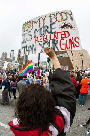 Atlanta, GA, USA - March 24, 2018:  A young woman holds a sign that says My body is more regulated than your guns at the March For Our Lives gun protest on March 24, 2018 in Atlanta, GA.