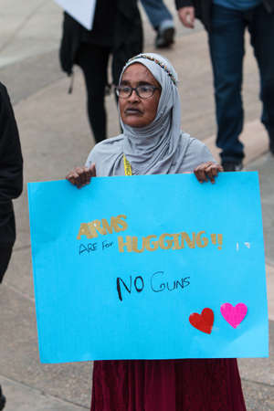Atlanta, GA, USA - March 24, 2018:  A Muslim woman stands and holds up a sign that says